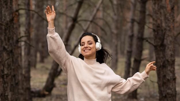 Smileyvrouw het luisteren muziek bij hoofdtelefoons