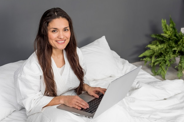 Smileyvrouw in bed met laptop
