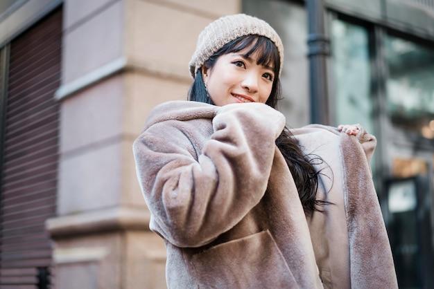 Smileyvrouw in de winteruitrusting die van haar dag in openlucht geniet