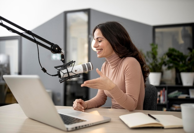 Smileyvrouw in een radiostudio met laptop en microfoon