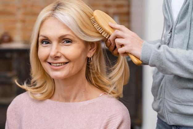 Smileyvrouw krijgt haar haar geborsteld in de salon door schoonheidsspecialiste