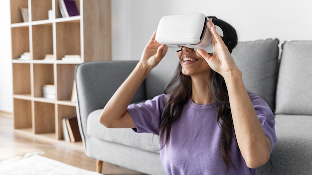 Smileyvrouw met behulp van virtual reality headset thuis