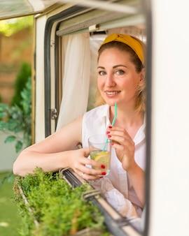 Smileyvrouw met een glas limonade naast een caravan