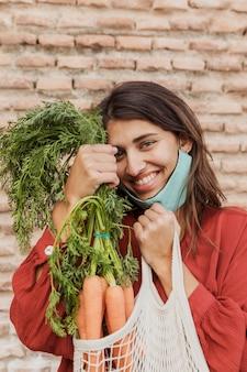 Smileyvrouw met gezichtsmasker die in openlucht wortelen houdt
