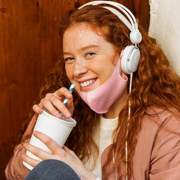 Smileyvrouw met gezichtsmasker in openlucht en hoofdtelefoons