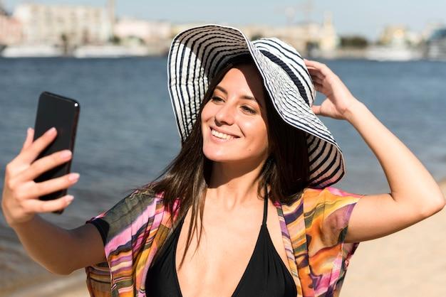 Smileyvrouw met hoed die selfie op het strand neemt