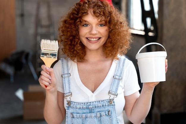 Smileyvrouw met penseel en emmer voor nieuwe huisdecoratie