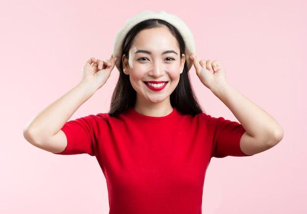 Smileyvrouw met rode lippen die haar hoed bevestigen