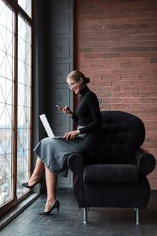 Smileyvrouw met telefoon en laptop