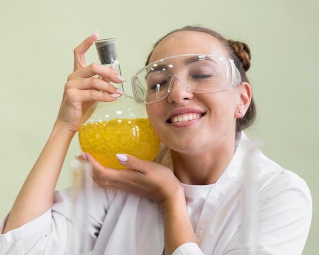 Smileyvrouw met wetenschapsexperimentbuis