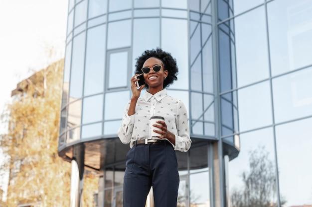 Smileyvrouw met zonnebril die over telefoon spreken