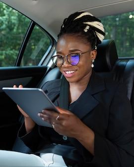 Smileyvrouw op de achterbank van haar auto die tablet bekijkt