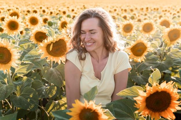 Smileyvrouw op zonnebloemgebied het stellen