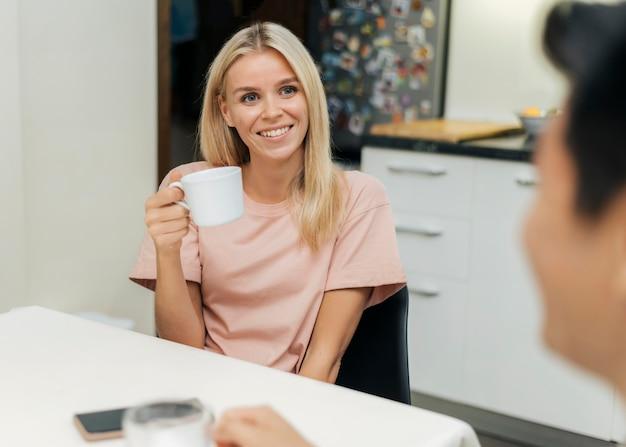 Smileyvrouw thuis tijdens de pandemie met een kopje koffie met haar vriendje