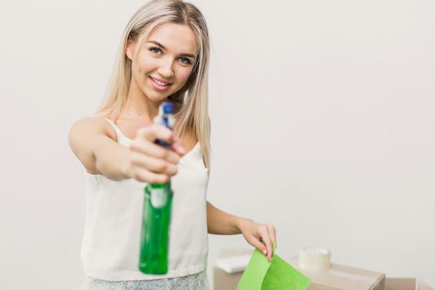 Smileyvrouw van de close-up met spary schoonmaken