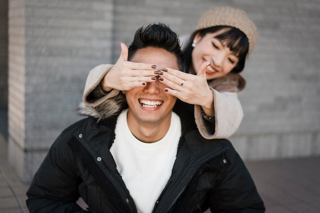Smileyvrouw verrast haar vriend buitenshuis