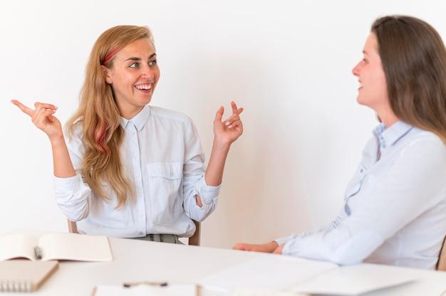 Smileyvrouwen communiceren met elkaar via gebarentaal
