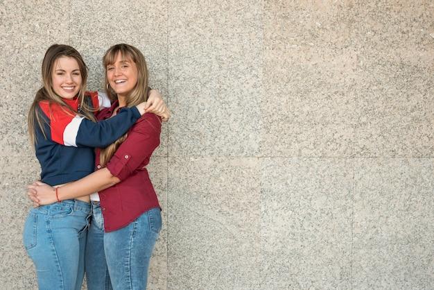 Smileyvrouwen die elkaar met exemplaar-ruimte koesteren