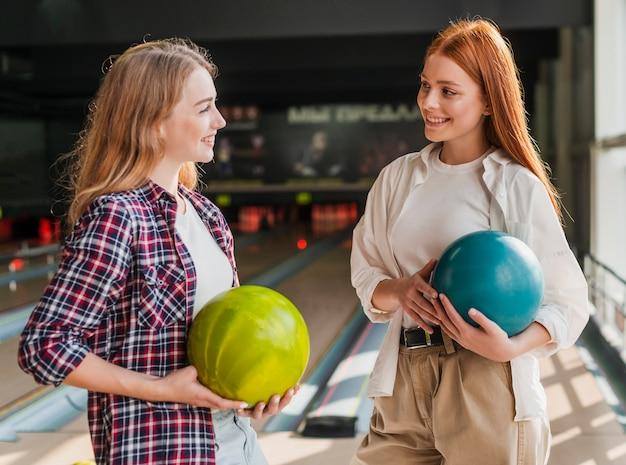 Smileyvrouwen die kleurrijke kegelenballen houden
