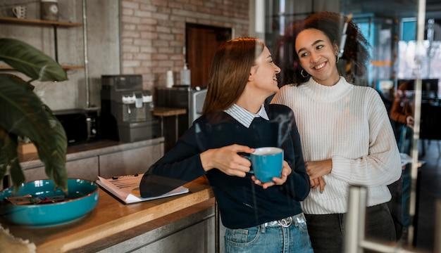 Smileyvrouwen die koffie drinken tijdens een vergadering