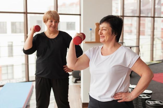 Smileyvrouwen die met gewichten werken
