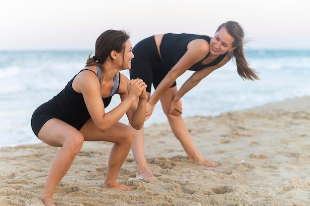 Smileyvrouwen die samen op het strand trainen