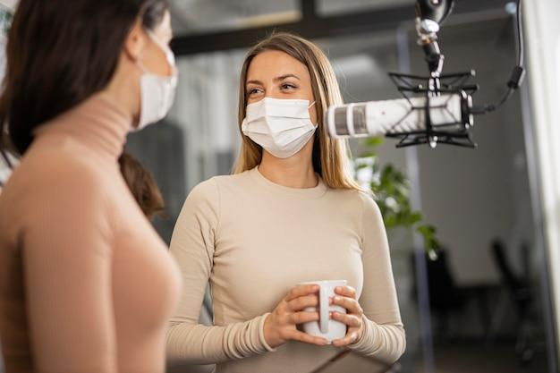 Smileyvrouwen die samen radio doen terwijl ze medische maskers dragen