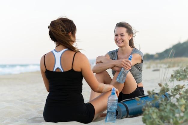 Smileyvrouwen die tijdens het sporten op het strand rusten