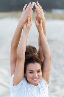 Smileyvrouwen die yoga op het strand doen