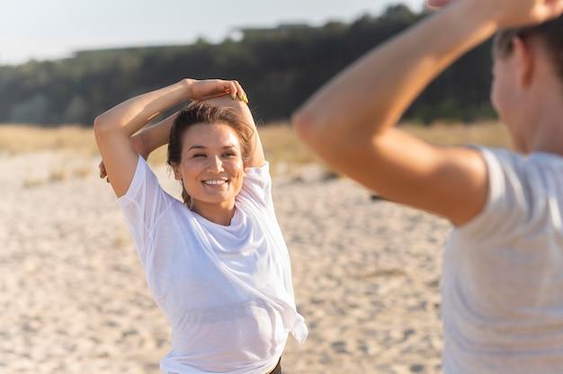 Smileyvrouwen die zich samen op strand uitstrekken alvorens uit te oefenen