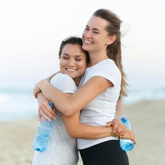 Smileyvrouwen knuffelen na het beëindigen van de trainingssessie