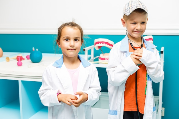 Smilg kleine jongen meisje medische uniform spelen met stethoscoop