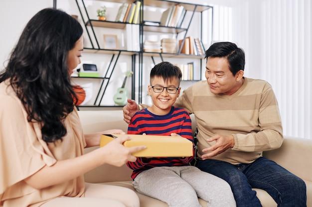 Smilig preteen jongen opgewonden om verjaardagscadeau van zijn ouders te krijgen