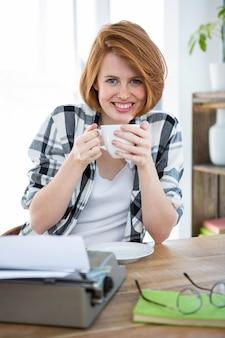Smilin hipster vrouw zit aan haar bureau koffie te drinken