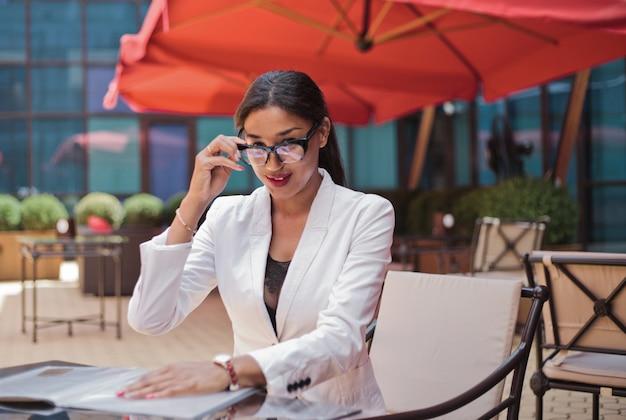 Smilling afro zakenvrouw klaar voor interview zittend aan tafel op terras en camera kijken