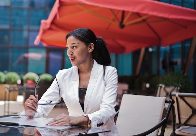 Smilling afro zakenvrouw klaar voor interview zittend aan tafel op terras