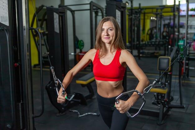 Smilling fit vrouw buigen spieren op gym machine. meisje voert oefening uit met oefenmachine cable crossover in moderne sportschool. fitness en bodybuilding