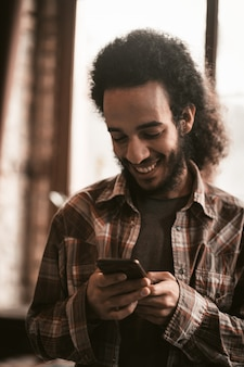 Smilling guy chatten op smartphone