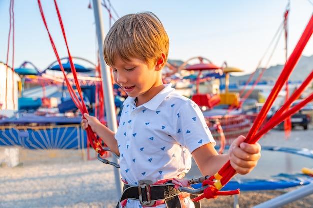 Smilling opgewekte jongen die op een trampoline met verzekering springt.