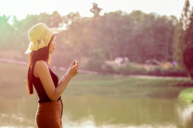Smillings aziatische vrouw met het licht van de zonsonderganggloed
