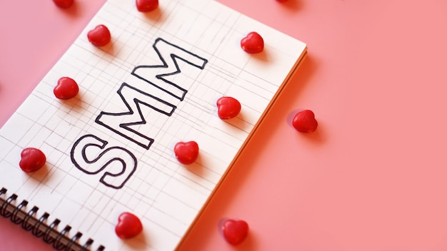 Smm social media marketingtekst op op notitieboekje op roze achtergrond met snoep in de vorm van harten