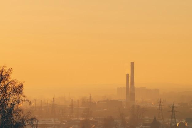 Smog onder silhouetten van gebouwen op zonsopgang.