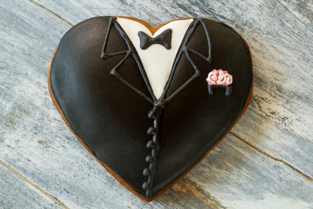 Smoking hart koekje. bruiloft cookie op houten achtergrond. smaak van de gelukkige dag. elegantie van bruidegom.
