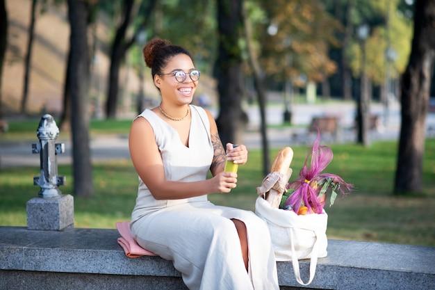 Smoothie drinken. vrolijke vrouw die smoothie drinken terwijl het zitten in park na het doen van boodschappen