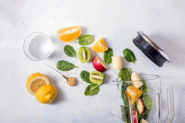 Smoothie-ingrediënten in mixer, smoothie-bereiding met spinazie, appel, sinaasappel, kiwi, gezond eten, detox en voedingsadvies