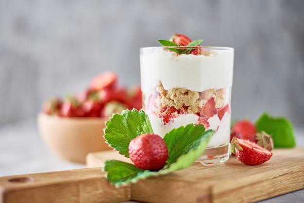 Smoothie met zomer aardbei in glazen pot en verse bessen in houten kom op een grijze