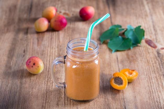 Smoothie van abrikoos en perzik in glazen mok