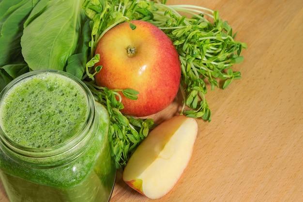 Smoothie voor gewichtsverlies in een glazen pot met ingrediënten op een houten snijplank