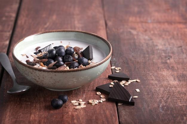 Smoothiekom met natuurlijke yoghurt, verse bessen en ontbijtgranen