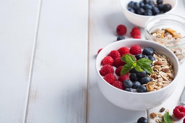 Smoothiekom met yoghurt, verse bessen en ontbijtgranen. grondstoffen voor een mooie dag